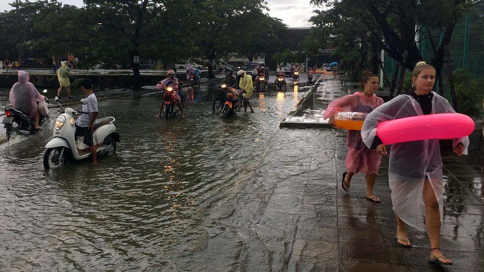 Tourists use rubber rings to cross a flooded road on Ko Samui, Thailand, 5 January 2017