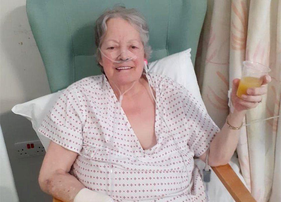 Mary Blessington drinking orange juice in hospital