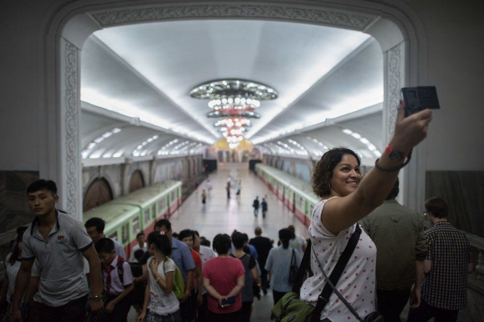 A tourist takes a selfie during a visit to a subway station in Pyongyang on 23 July 2017.