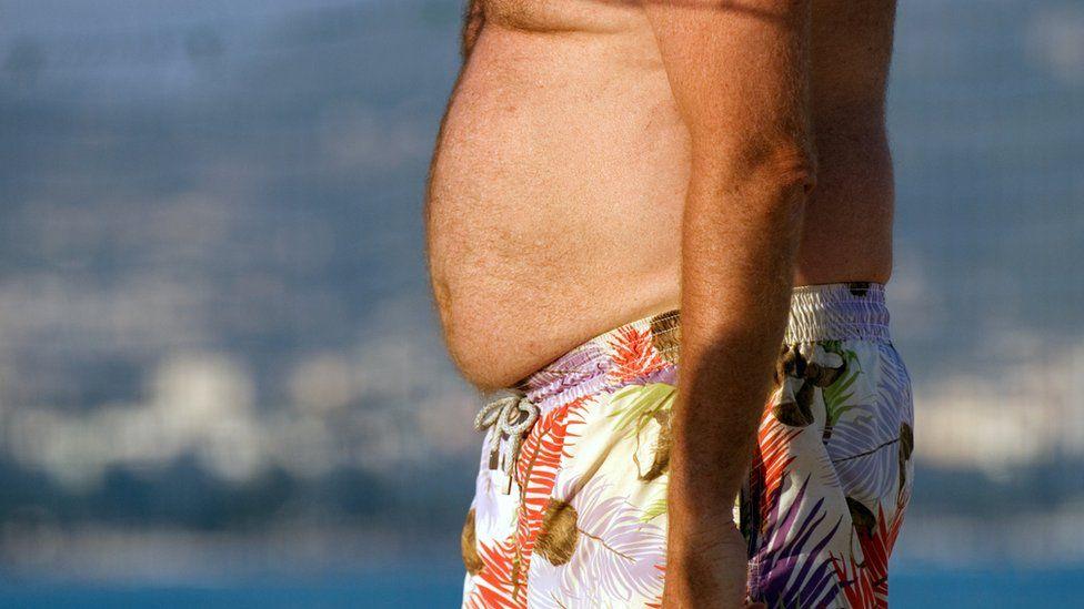 Man's midriff in beach shorts on beach