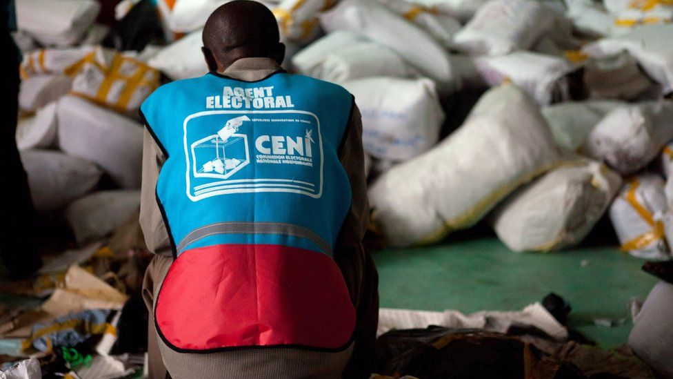 An electoral agent of the National Independent Electoral Commission (CENI) sits on a bag of ballot papers in a warehouse in Kinshasa on December 3, 2011