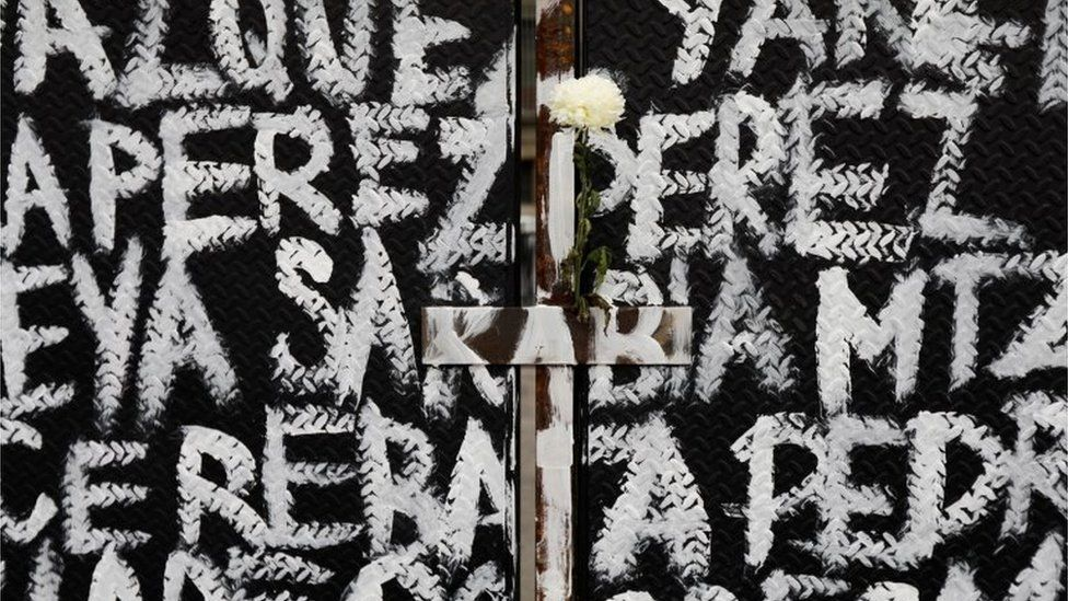 "A flower is seen among the names of victims of femicide in Mexico painted by women on fences placed outside the National Palace ahead of a Women""s Day protest in Mexico City, Mexico March 7, 2021"