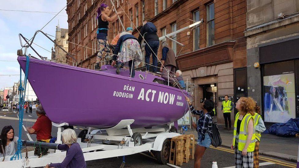A purple boat blocks a road in Glasgow