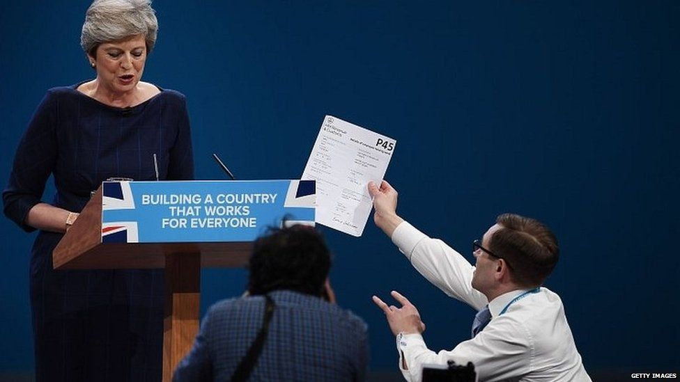 Comedian Simon Brodkin handing a piece of paper to the prime minister