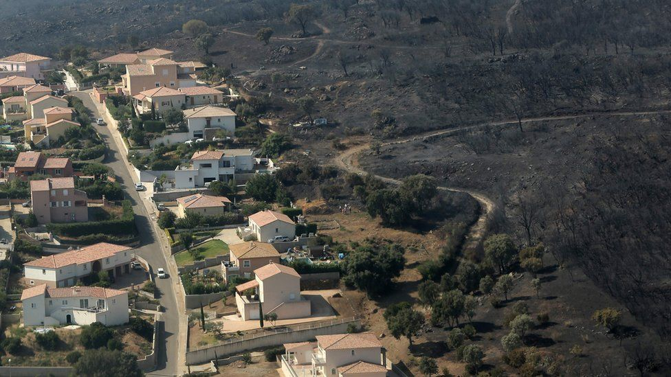 An aerial view taken on July 25, 2017 shows the fire devastated landscape in Biguglia, on the French Mediterranean island of Corsica.