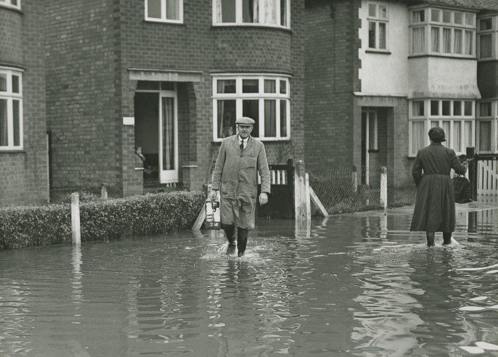 Milkman delivers during a flood