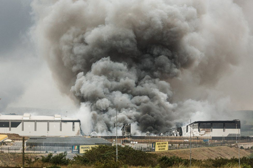 Smoke rises from a Makro building set on fire overnight in Umhlanga, north of Durban, on 13 July 2021