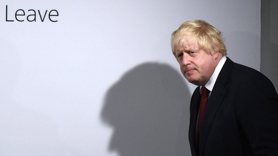 """Boris Johnson at a post-vote press conference; The word """"leave"""" is written on the wall behind"""