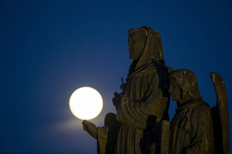 The pink supermoon rises behind statues on Charles Bridge in Prague, Czech Republic