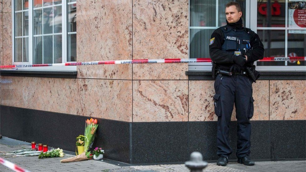 A policeman stands next to some flowers left at the scene of the shooting in Hanau