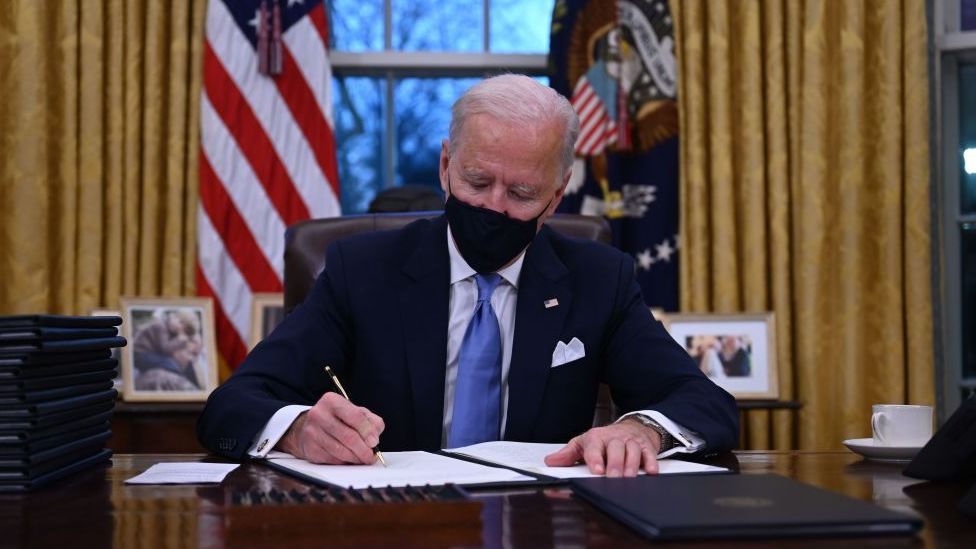President Biden signing papers at his desk