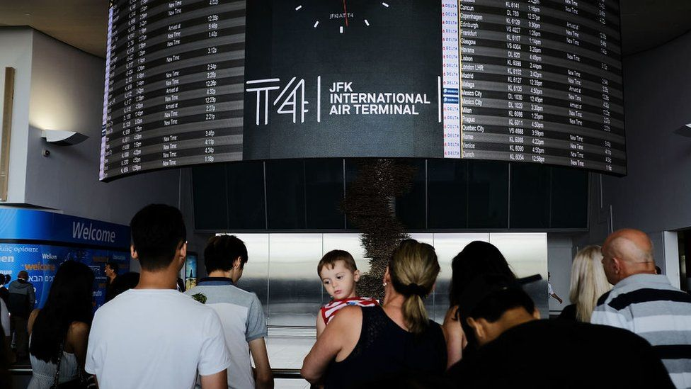 People walk through international arrivals at terminal four at John F Kennedy (JFK) airport