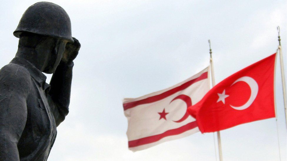 A soldier statue is seen with Turkish (R) and TRNC (self-proclaimed Turkish Republic of Northern Cyprus) flags 15 November 2006 in Nicosia