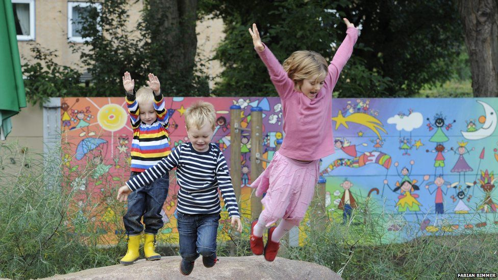 Children playing in front of a noise barrier in Germany