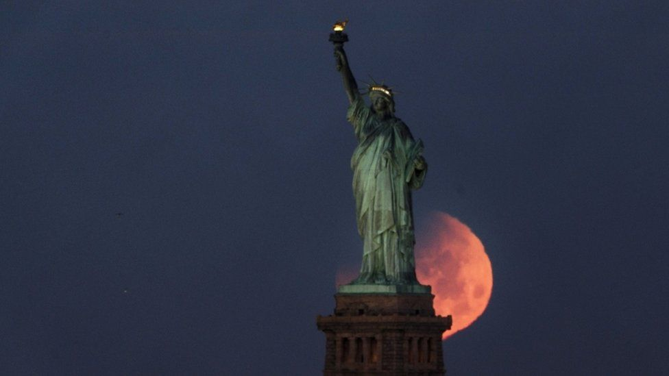The statue of liberty is seen with pink glowing moon, large around its base