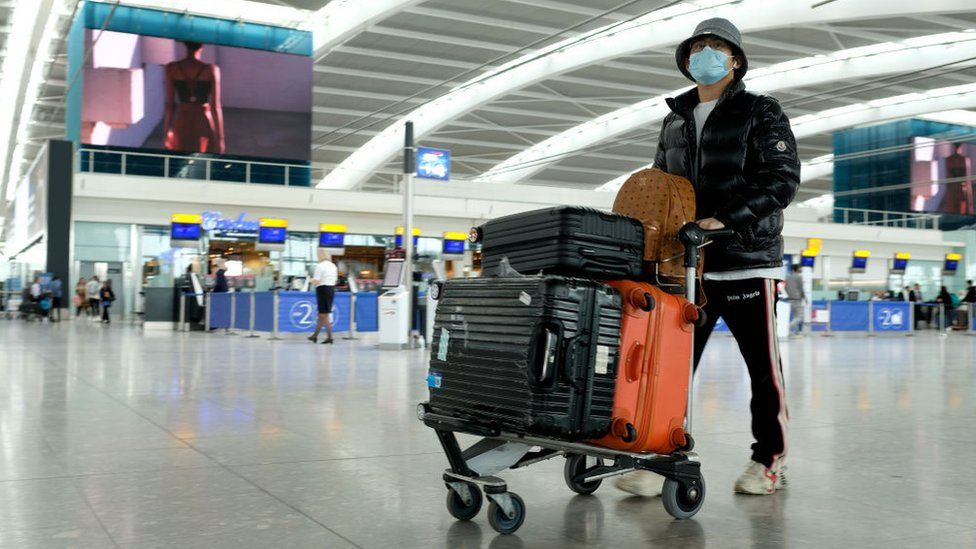 Man wearing mask pushes trolley through airport