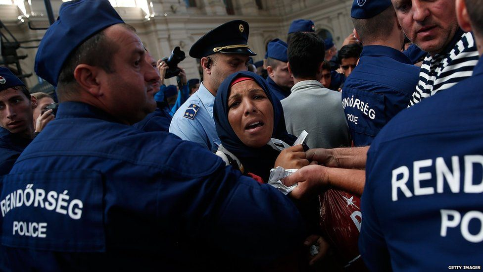 An Iraqi woman struggles with Hungarian police after being separated from her family while attempting to board a train bound for Vienna, Austria at the Keleti railway station on 8 September 2015 in Budapest, Hungary