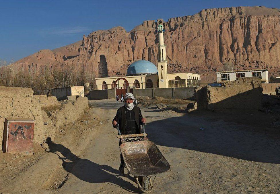 A Hazara man pushes a wheelbarrow along a road near the site of the Buddhas of Bamiyan statues
