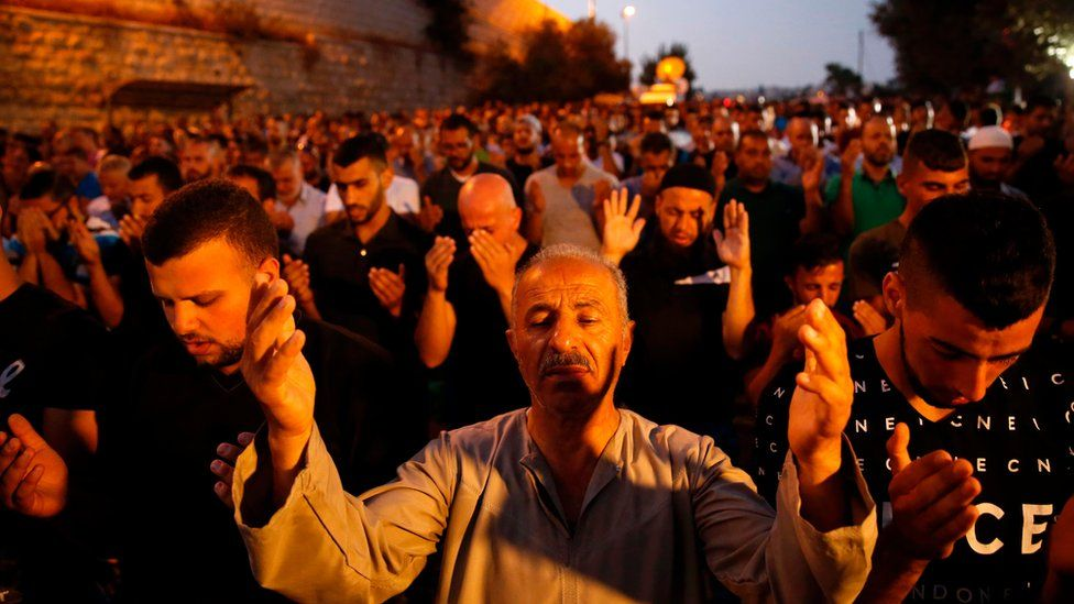 """Palestinian Muslim worshippers pray outside Lions' Gate, a main entrance to the Al-Aqsa mosque compound in Jerusalem""""s Old City, on July 22, 2017, in protest against new Israeli security measures implemented at the holy site following an attack that killed two Israeli policemen the previous week."""
