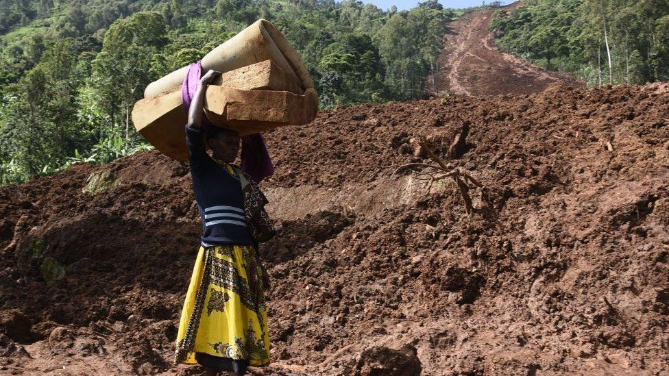 A woman carries a rolled-up mattress at a landslide site in Shisakali village of Bududa district, eastern Uganda,