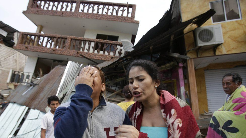 A woman weeps outside a house destroyed in Ecuador's earthquake