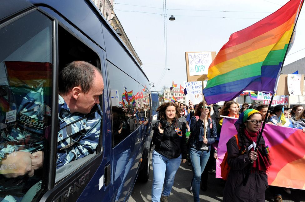 A Russian policeman watches a rally by LGBT activists, 1 May 15