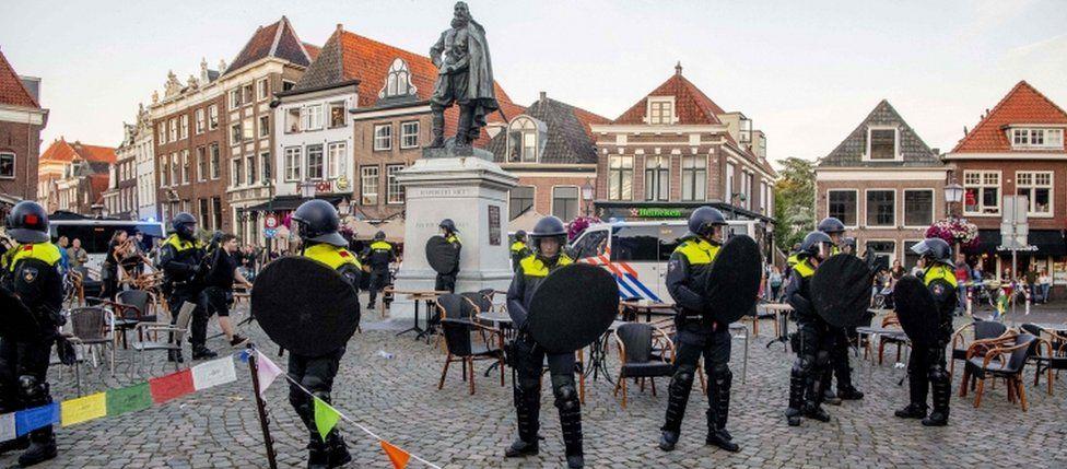 Police stands guard around the statue of Jan Pieterszoon Coen in Hoorn, on June 19, 2020