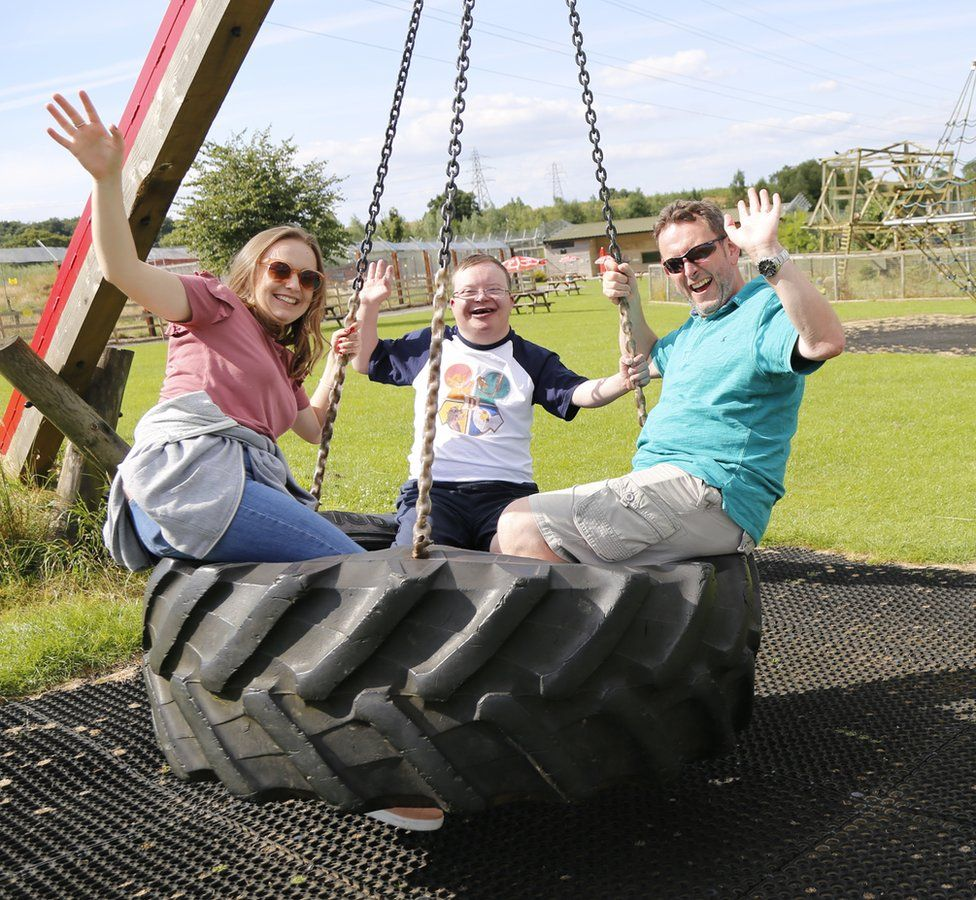 Three people on a big tyre swing - Paul Fears is on the right, his disabled son Greg in the middle and his daughter Megan on the left