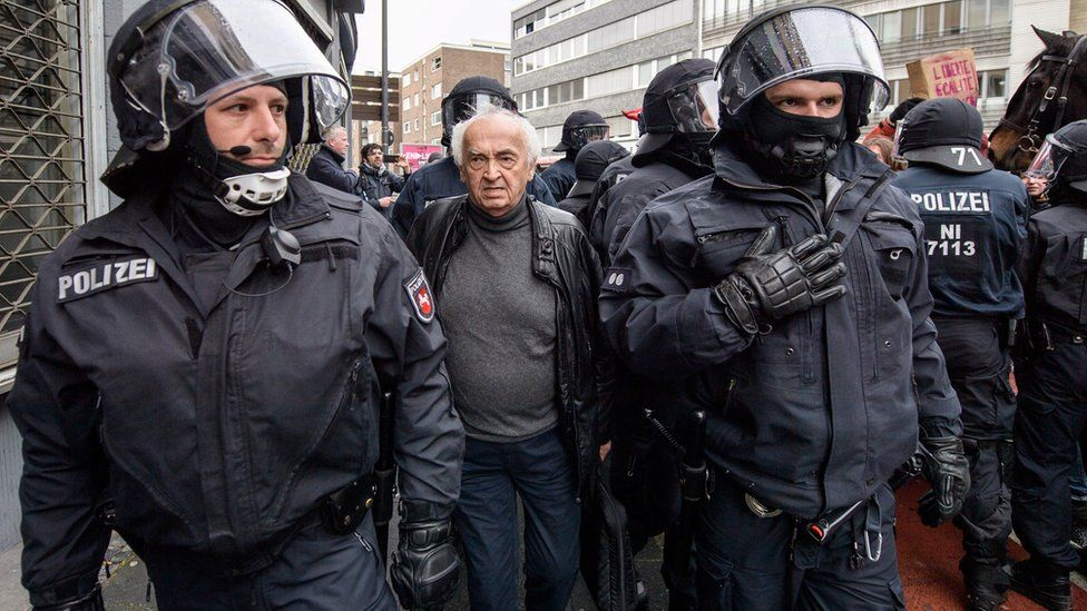 officers in riot gear flanking an elderly man