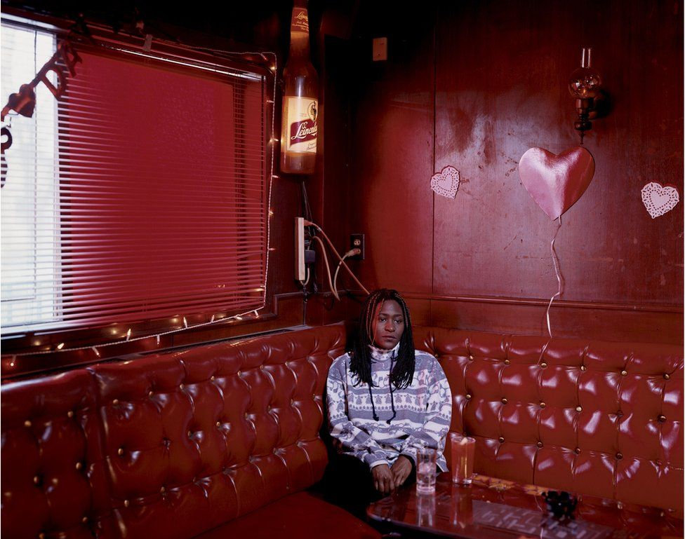 Kym sits in the corner of a nightclub with red walls and sofas