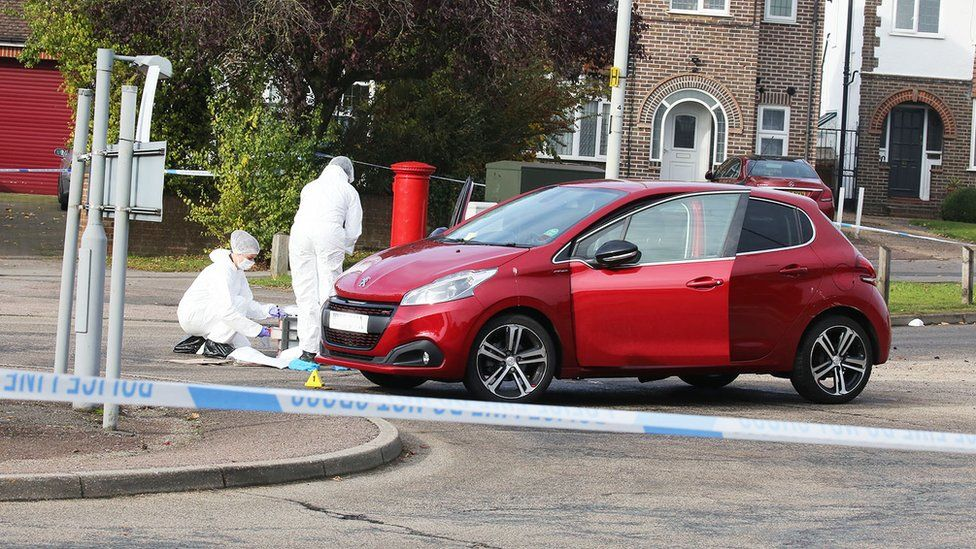 Police investigators with a red Peugeot car