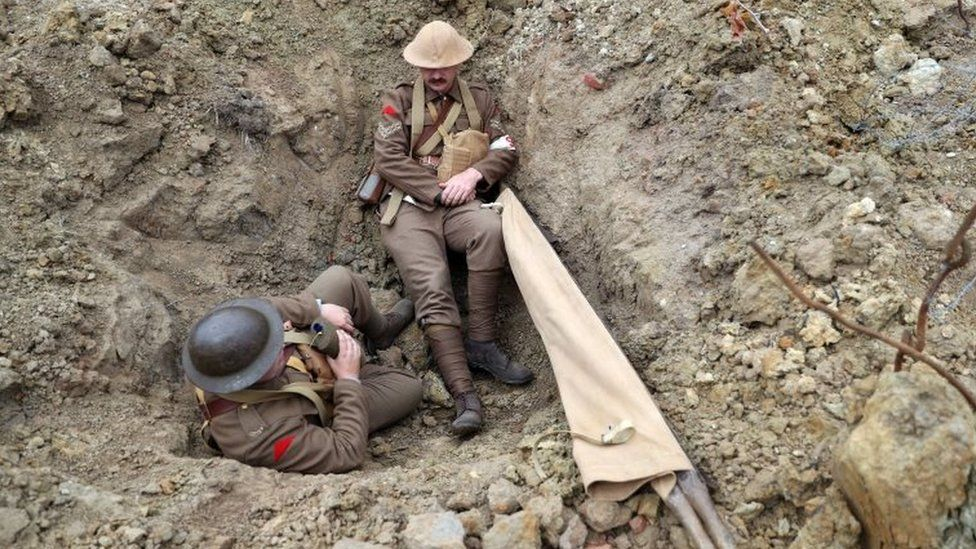 "World War One re-enactors sit in the ""Passchendaele Landscape"", a recreation of the 1917 conditions on the battlefield at the Passchendaele Memorial Park in Zonnebeke"