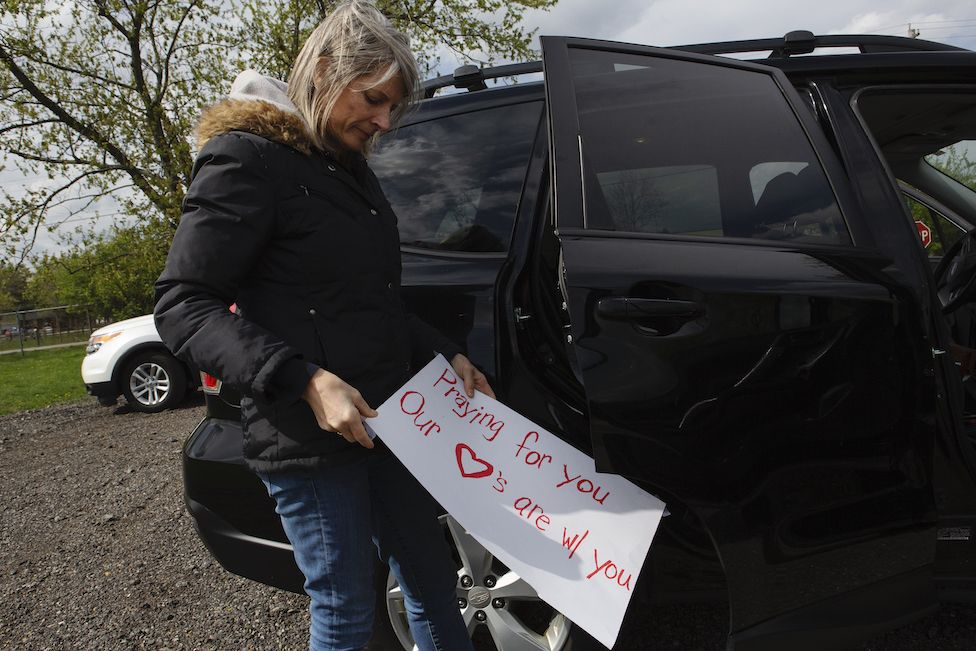 Maddie's mom Karen holds a sign for makeshift funeral procesion for a colleague