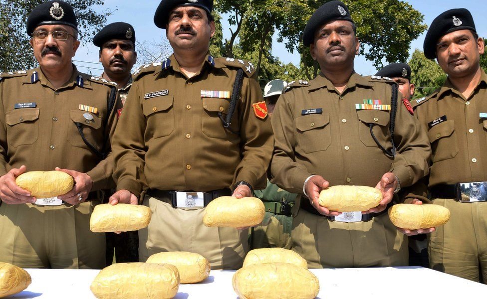 Indian Border Security Force (BSF) Deputy Inspector General MF Farooqui (C) poses for a photograph while holding confiscated parcels of heroin, recovered near the border with Pakistan, at the BSF headquarters in Khasa, some 20 kms west of Amritsar on February 24, 2014.