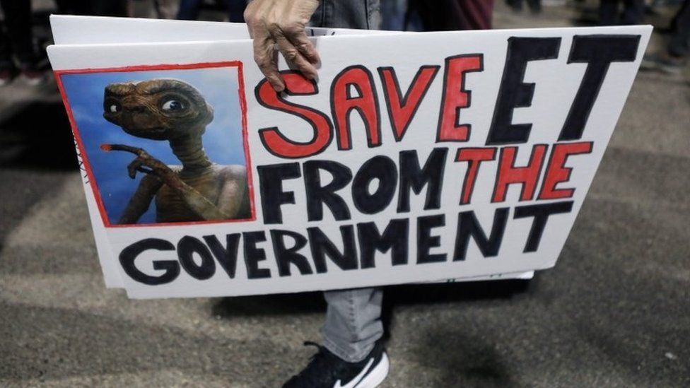 A person carries signs outside a gate to Area 51