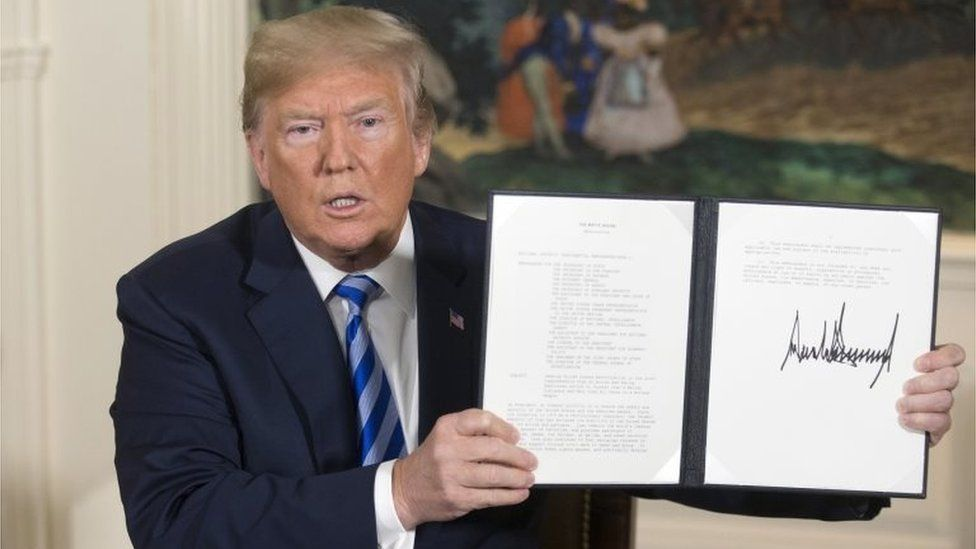 Donald Trump holds up presidential memorandum pulling the US out of the Iran nuclear deal