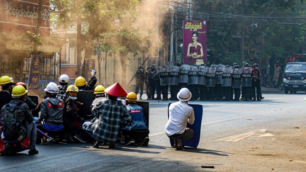 Protesters sit in a street holding makeshift shields as they face police in riot gear, in Mandalay on 3 March 2021
