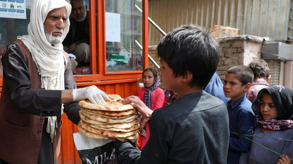 File photo showing an Afghan boy receives free bread outside a bakery in Kabul (3 May 2020)