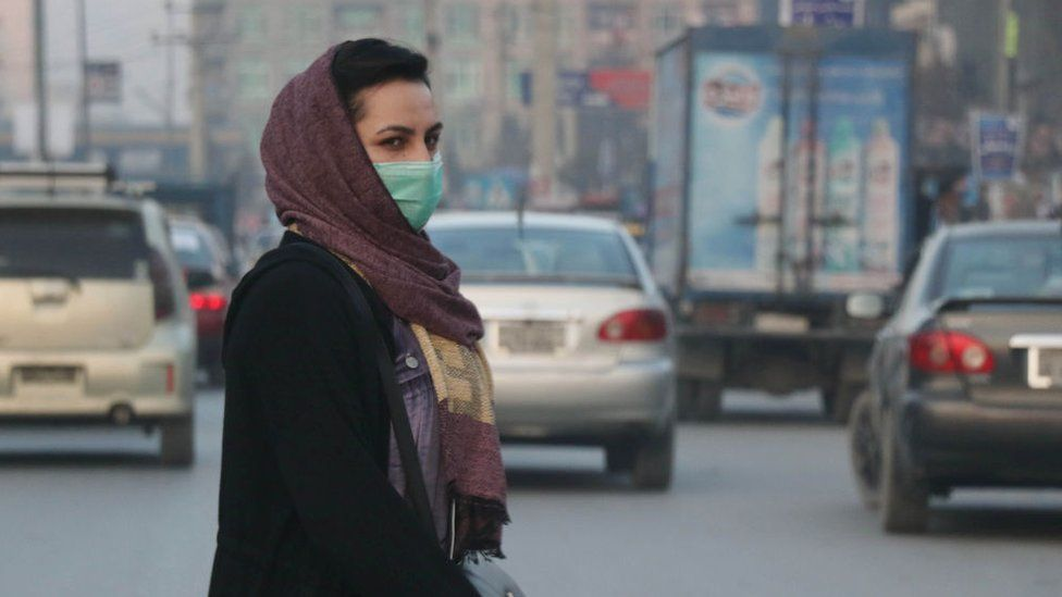 An Afghan woman wears a face mask as she walks in a busy Bazar in Kabul, Afghanistan on December 23, 2020