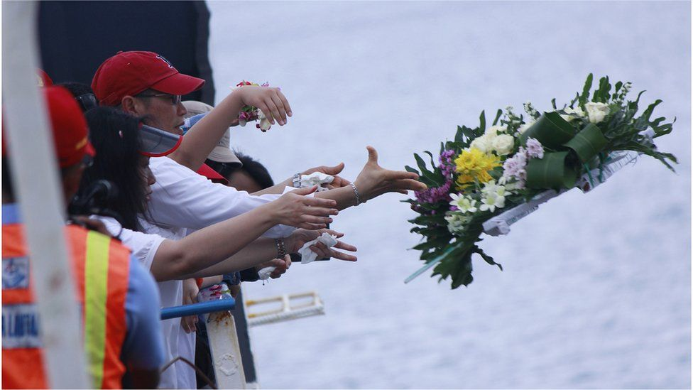 Relatives of victims of AirAsia flight QZ8501 throw a flower wreath into the sea in Central Kalimantan on 22 March 2015