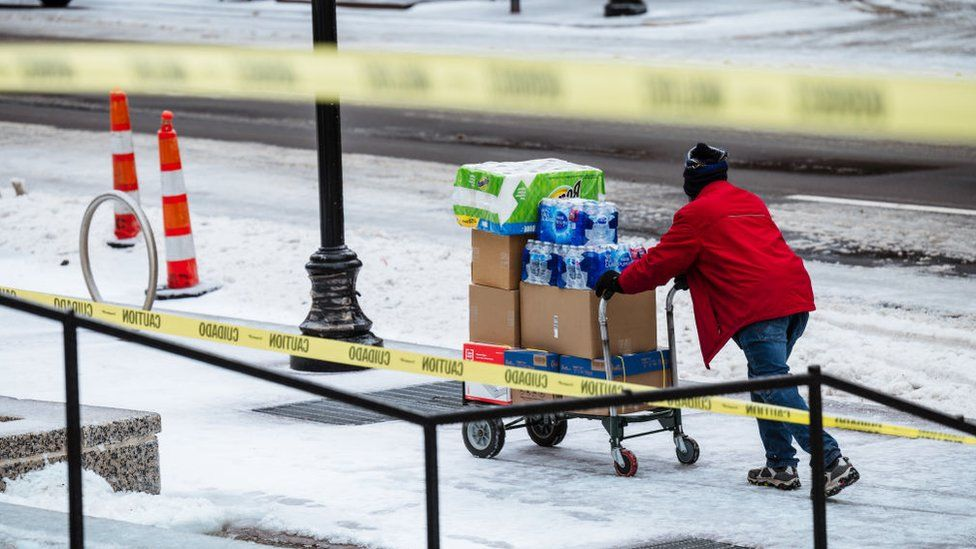 A delivery driver pushes a cart full of supplies down an icy sidewalk on February 11, 2021 in Louisville, Kentucky
