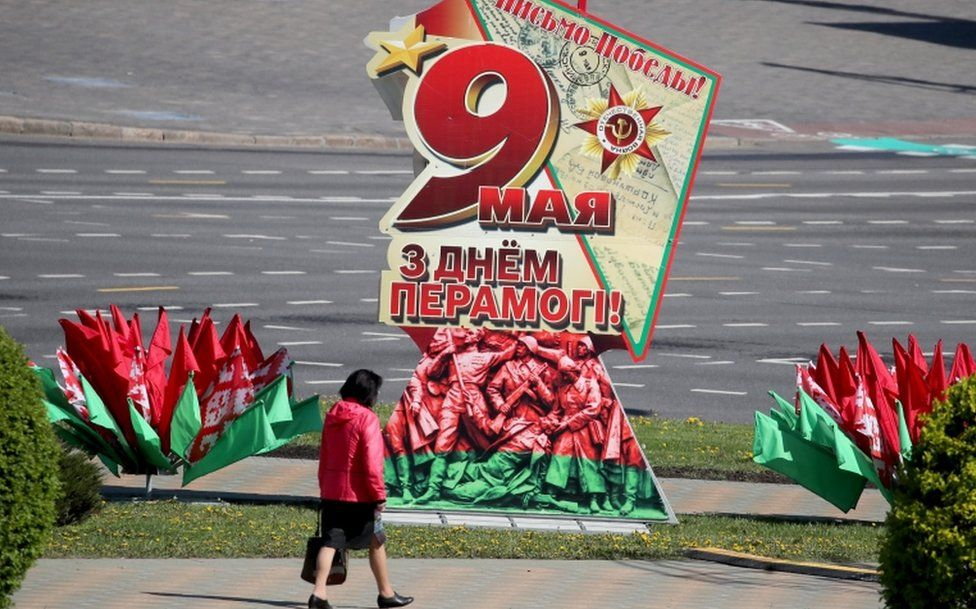 A woman walks past a patriotic placard as Minsk prepares to celebrate Victory Day, 7 May 2020