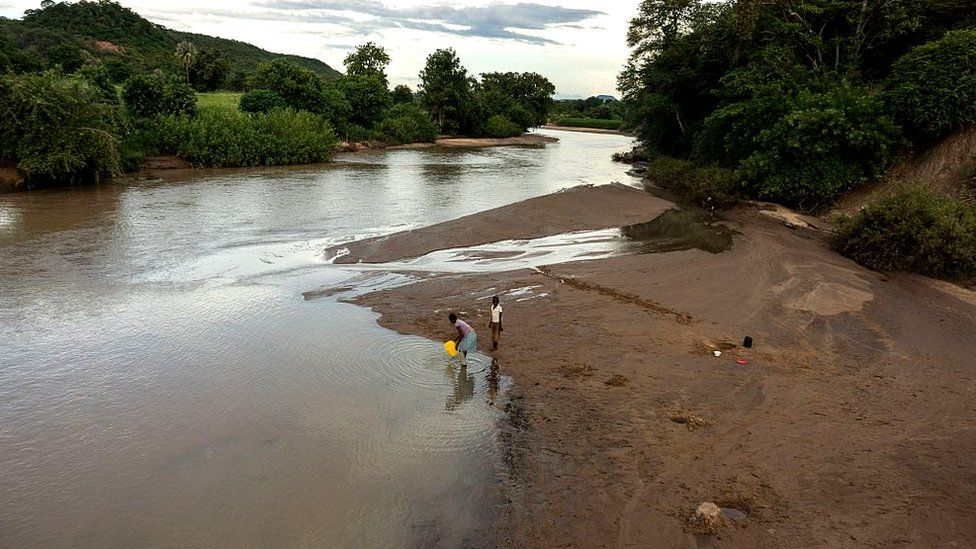 Two people fetch water from a river on the outskirts of Siachilaba village, Binga district in Matabeleland North Province, Zimbabwe, on January 24, 2017