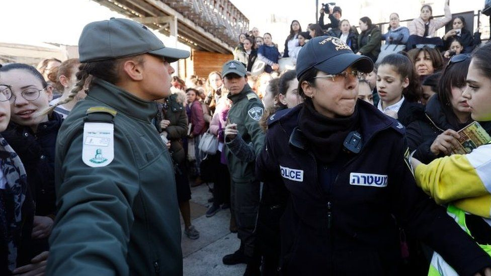 Israeli policewomen hold back Ultra Orthodox Jewish girls gathering at Judaism's holiest prayer site of the Western Wall in the Old City of Jerusalem on 8 March 2019