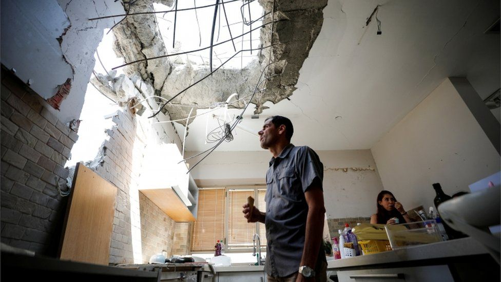 A man in Ashkelon looks at the damage done to his house by a rocket fired from Gaza