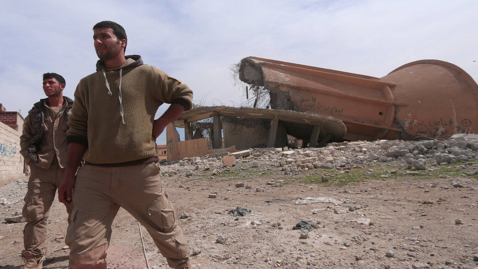 Syrian Democratic Forces fighters walk among damaged buildings to the east of Raqqa