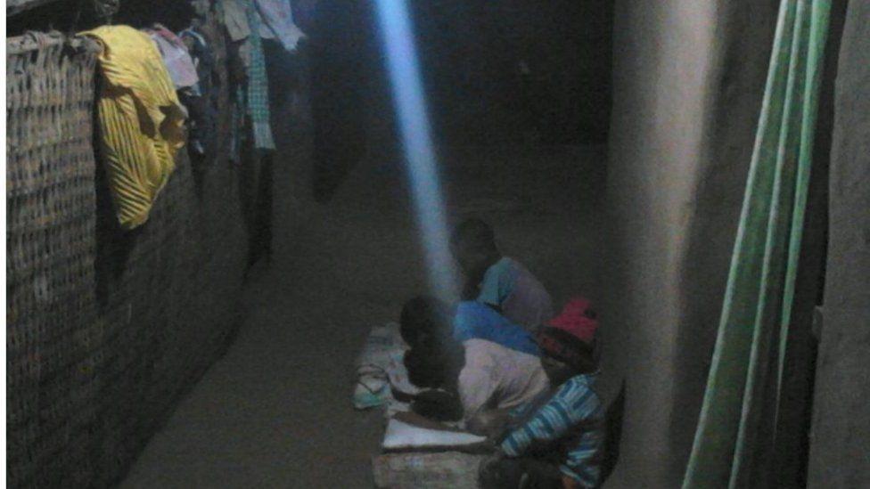 Village children study under electric light