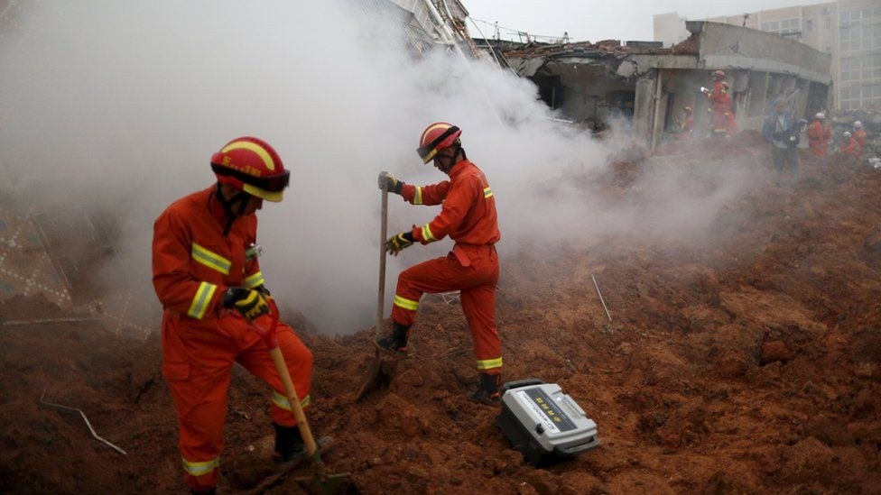 Firefighters search for survivors as smoke rises from a damaged building at the site of a landslide at an industrial park in Shenzhen, Guangzhou, China, December 20, 2015.