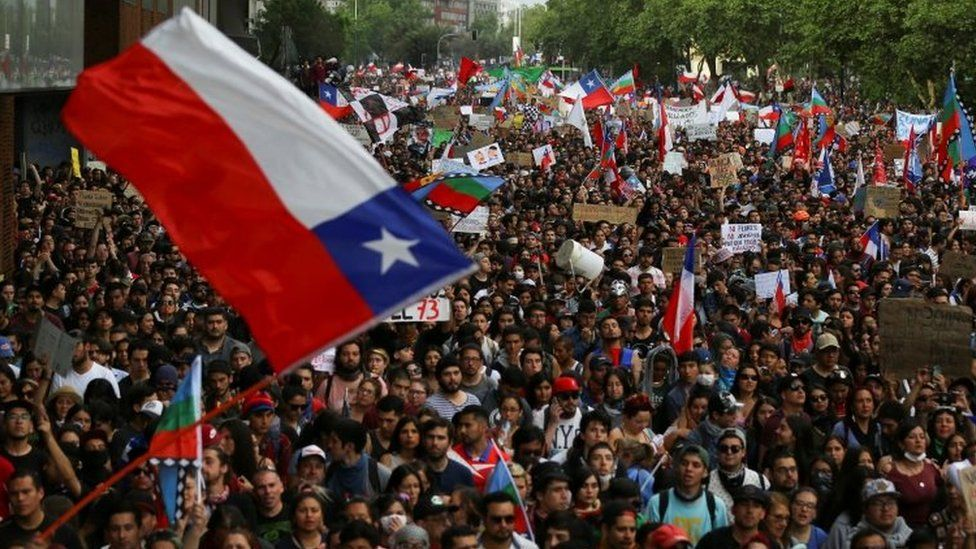 """Demonstrators march with flags and signs during a protest against Chile""""s state economic model in Santiago, Chile October 25, 2019"""