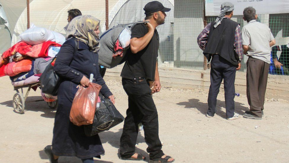 Syrians carry their belongings at a camp in rebel-held Idlib province after being evacuated from the Damascus district of Qaboun (15 May 2017)